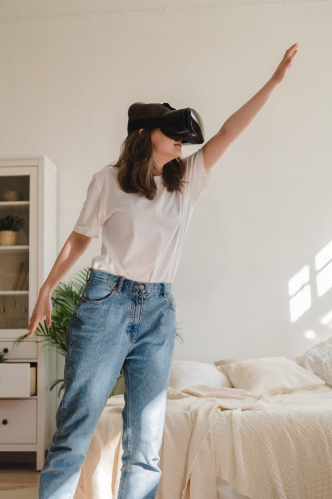 Young woman in jeans and white T-shirt wearing virtual reality helmet plays game, works