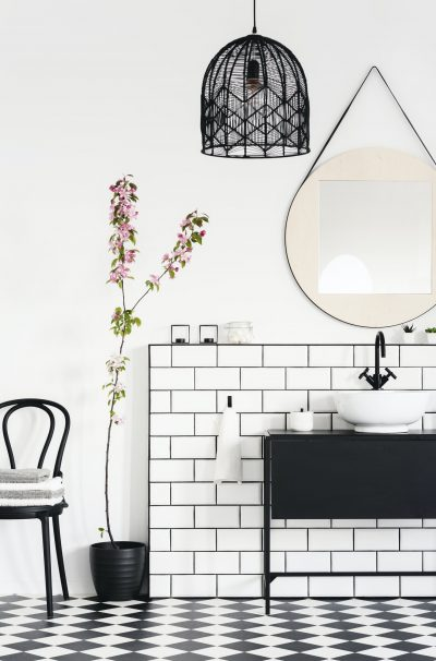Lamp and mirror above black washbasin in modern bathroom interio
